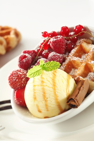 Tilted perspective of a serving of a crisp golden waffle with an assortment of fresh red berries and ice-cream photo