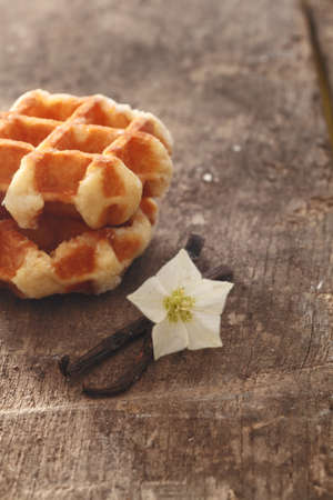 flavouring: Dried vanilla pods and flower used as flavouring in cooking and baking on a wooden surface with golden waffles Stock Photo
