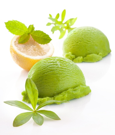 Scoops of fresh green lemon or lime icecream on a white studio background with faint reflection photo