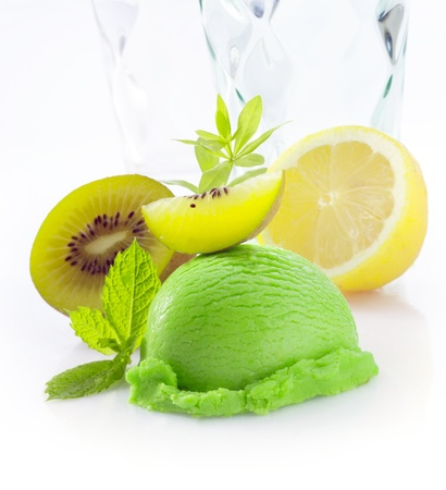 woodruff: Creamy green tropical kiwi fruit icecream with fresh sliced kiwi fruit and lemon on a white background