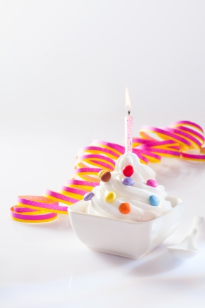 europe closeup: Party ice-cream dessert in a square dish with a single burning birthday candle and spirally coiled decorative ribbon with copy space Stock Photo