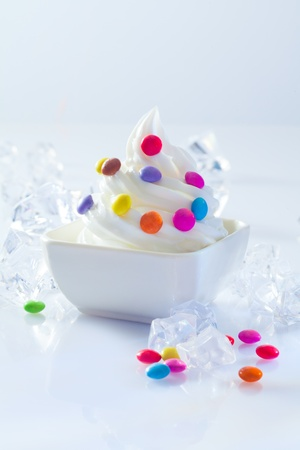 Individual serving od soft-serve icecream dessert dotted with colourful round candy ready for a childs birthday party photo