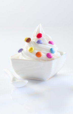 frozen joghurt: Twirled serving of soft-serve icecream covered in colourful round sweets on a white background