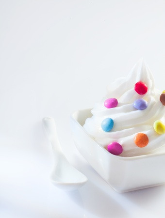 frozen joghurt: Soft-serve icecream whirl with colourful round candy ready for a childs bithday party with copyspace Stock Photo
