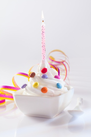 frozen joghurt: Festive and Birthday Dessert with candle. Frozen Yogurt served with sweet candies topping and paper streamer for birthday concepts