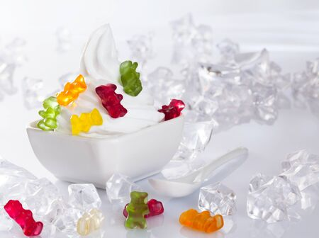 frozen joghurt: Cold Frozen yogurt Dessert served with ice cubes and brightly gummi bears