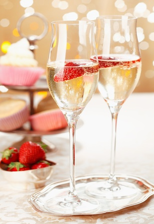 champagne flutes: Romantic champagne and strawberries served on a silver tray in elegant flutes with festive party lights