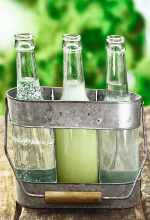urban gardening: Three refreshing healthy drinks of pure fresh aerated and still water and fruit juice served in clear glass bottles in a rustic metal holder