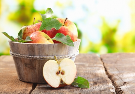 Wooden tub full of freshly harvested red apples with a halved apple on display on a wooden tabletop outdoors with copyspace Stock Photo