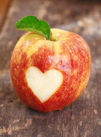 Ripe red apple with a heart shape neatly cut of the skin on a textured weathered wooden surface photo