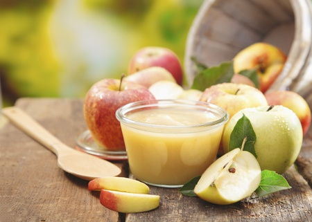 field glass: Preparing apple puree or sauce in a small glass jar with sliced apple pieces and a wooden spoon on an old wooden table outdoors