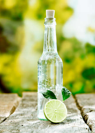 corked: Pure fresh aerated water in a corked glass bottle with sliced lemon on a textured wooden tabletop Stock Photo