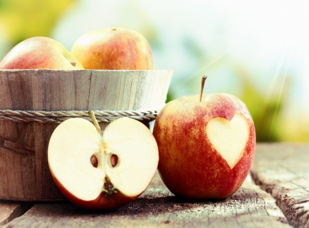 Rijpe rode appel stilleven display met een gehalveerde appel en een appel met een hart uitsnede leunend tegen een houten bad gevuld met hele vrucht. Bezoek mijn portfolio voor hele reeks.