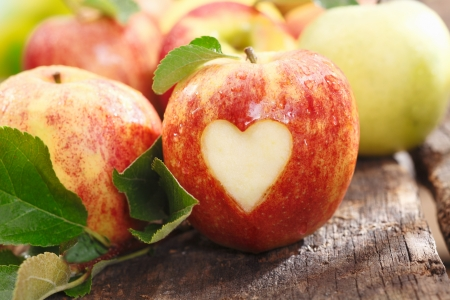 Fresh red apple on an old textured weathered wooden table with a heart cutout