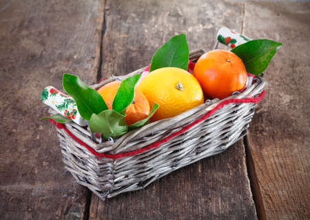 Fresh colourful country oranges in a wicker basket with leaves standing on a rustic grunge wooden background photo