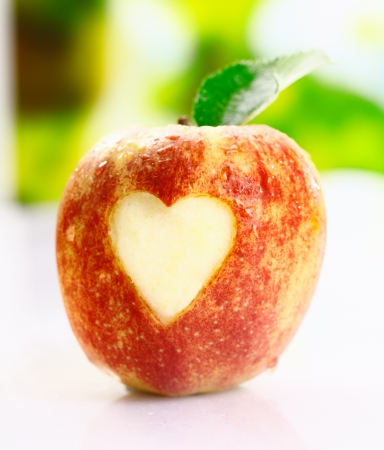pic: A juicy fresh ripe red apple with an incised heart shape in the skin conceptual of I love apples Stock Photo