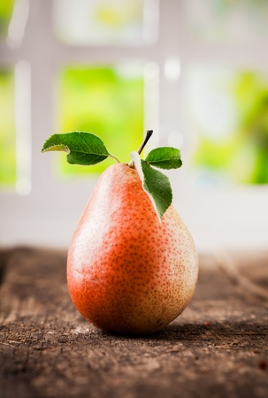 Tasty ripe red and yellow pear with leaves on a rough wooden table indoors with window background photo