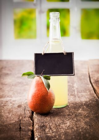 A juicy ripe red pear stands alongside a bottle of natural freshly squeezed pear juice with a blank slate on display on a wooden table photo