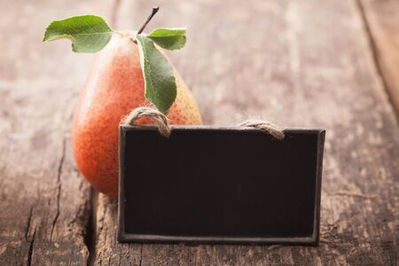 Fresh ripe red and yellow pear with a blank blackboard slate for your text on an old wooden table photo