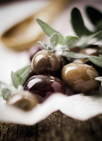 Deliciouss fresh black olives and leaves with shallow depth of field and copyspace photo