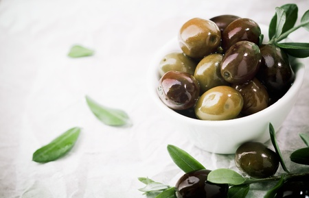 greek cuisine: Bowl filled with fresh black olives served as an accompaniment or appetizing snack with copyspace