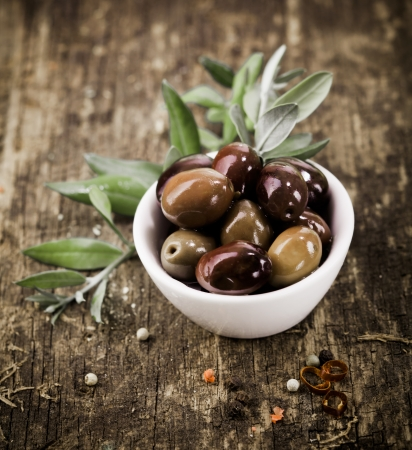 olive leaves: Bowl filled with freshly harvested whole fresh black olives on a rustic wooden tabletop