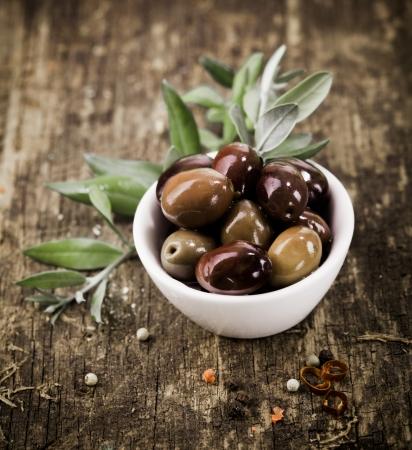olive leaf: Cuenco lleno de reci�n cosechadas aceitunas negras frescas sobre una mesa de madera r�stica