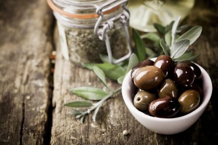 Een kom van verse zwarte olijven en de verpakking van gedroogde kruiden staan op een oude houten keukentafel voor gebruik als ingrediënten in de keuken Stockfoto