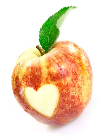 Luscious red apple with a heart cutout in the skin signifying love of fresh healthy organic fruit photo