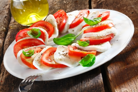 fruity salad: Colourful slices of cheese and tomato arranged alternately on a plate and garnished with herbs served with an oil dressing for drizzling Stock Photo