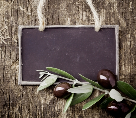Fresh black olives on a leafy twig and a blank slate for your text lying on an old weathered wooden table
