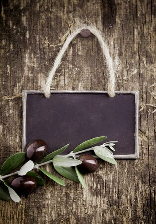 Fresh black olives lying with a slate blackboard on an old grungy weathered and textured wooden table Stock Photo - 14759885