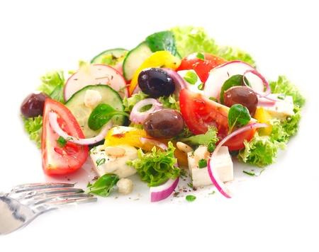 Servir la ensalada griega deliciosa con verduras frescas, queso feta, aceitunas, tomate y cebolla con guarnición de piel de naranja