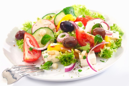Healthy Greek salad served for lunch with crisp leafy greens, olives, feta, onion , tomato, cucumber and radish on a white background photo