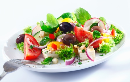 Healthy mixed Greek salad served on a white plate with silver fork containing crisp leafy greens, olives, feta, onion , tomato, cucumber and radish