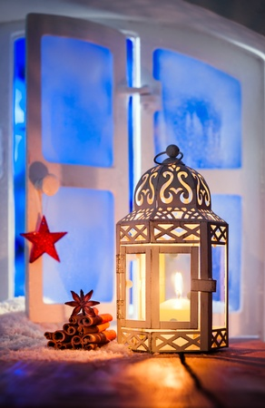 Christmas lantern with a glowing candle burning in a window illuminating dried seasonal spices with copyspace photo