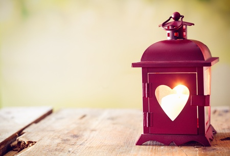 Decorative red metal lantern with a heart cutout lit by a glowing candle with copyspace for Valentines or Christmas