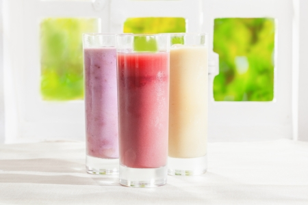 Variety of healthy fresh fruit t smoothies in glasses made from a blend of creamy yoghurt and liquidised fruit photo