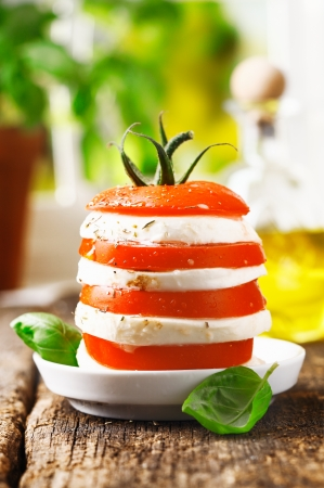 alternating: Cheese and tomato tower with alternating slices of fresh ripe red tomato and cheese served on a rustic wooden table