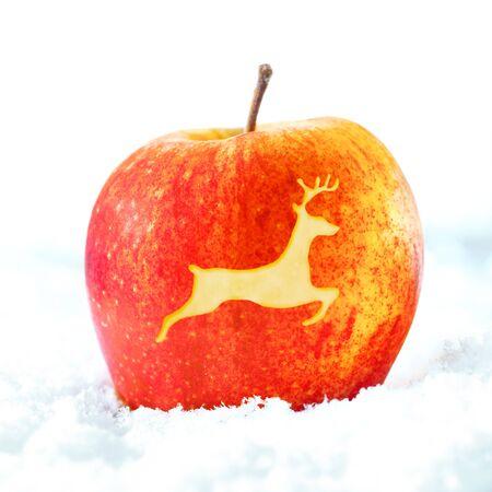 christmas apple: Ripe mela rossa decorativa di Natale con la forma di una renna che salta inciso su pelle