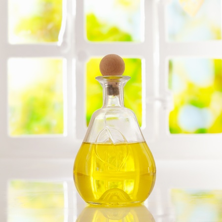 atmospheric: Glowing golden olive oil in a stoppered glass container for dispensing for cooking or as a salad dressing backlit by a bright airy window