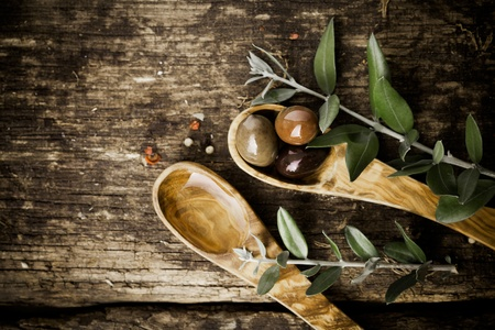 Olive wood spoons with fresh olives and leaves on an old grungy textured wooden tabletop with copyspace photo