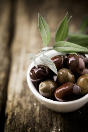 mediterranean cuisine: Fresh black olives in a bowl for appetizers to be served with drinks before a meal with copyspace