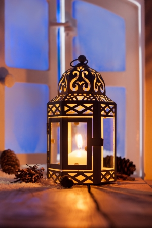 christmas atmosphere: Ornamental Christmas lantern with a glowing candle illuminating a window in the evening light