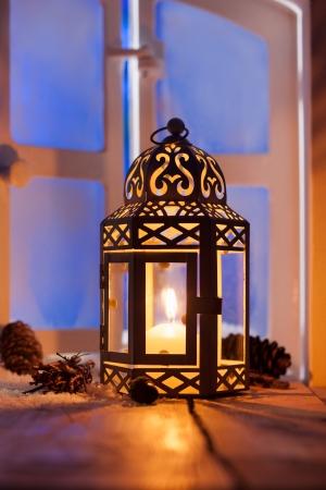 Sier Kerst lantaarn met een gloeiende kaars verlichting van een venster in het avondlicht Stockfoto