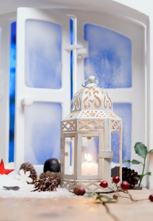 christmas atmosphere: Pretty white Christmas lantern with a burning candle on a windowsill surrounded by decorative cones and berries