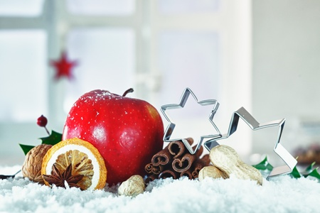 Beautiful Christmas still life with stars balanced on dried fruit, nuts and spices and a festive red apple nestling in snow with copyspace photo