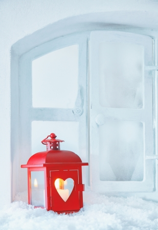 Cheerful red Christmas lantern with a glowing candle standing on a snowy windowsill with copyspace for seasonal greetings photo