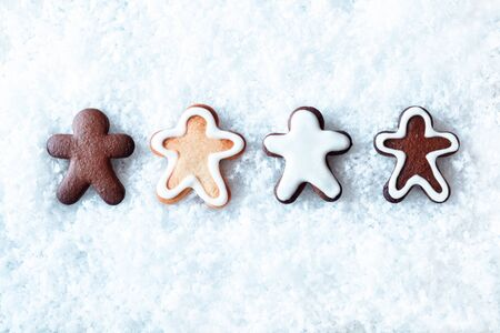 christmass: Row of decorative freshly baked gingerbread men lying on fresh snow with copyspace above and below for Christmas or seasonal greetings