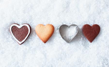 galletas de navidad: Rom�ntico galletas de Navidad del coraz�n con pan de jengibre y un coraz�n en forma de molde de metal en una l�nea en la nieve fresca con copyspace arriba y abajo para los saludos de temporada